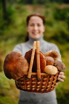 Close-up van eetbare paddenstoelen in een rieten mand in de handen van een wazig meisje selectieve focus