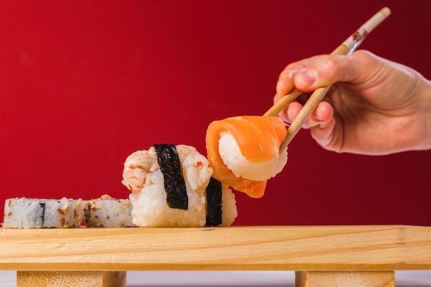 Close-up van eetstokjes die een deel van sushibroodje met zalm nemen.