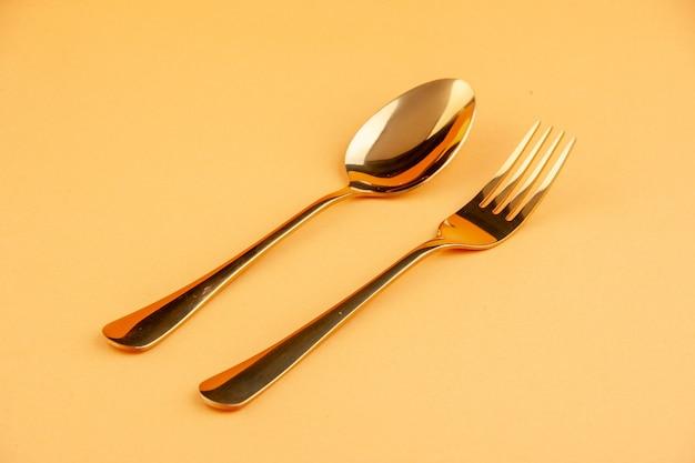 Close-up van elegante glanzende gouden rvs lepel en vork op geïsoleerde gele achtergrond met vrije ruimte