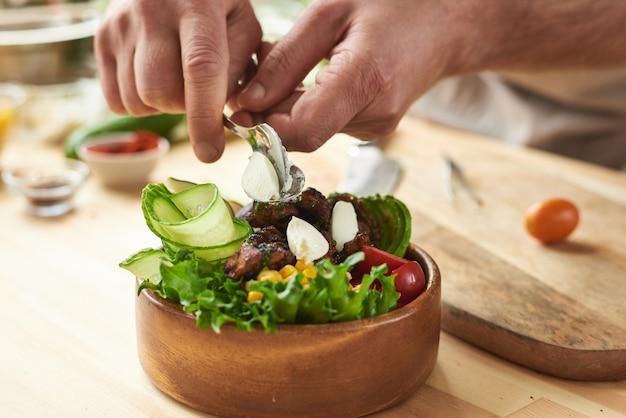 Close-up van elegante houten kom met verse groenten en vlees bereid door chef-kok