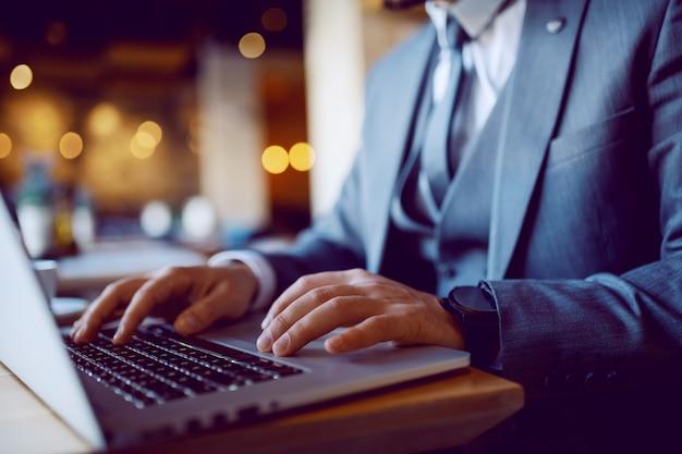 Close up van elegante zakenman in pak in café zitten en laptop gebruikt. handen zijn op toetsenbord. selectieve aandacht voor handen.