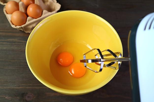 Close-up van elektrische eiklopper gaan een paar rauwe eieren in mengkom slaan