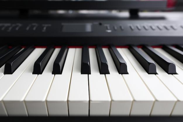 Close-up van elektronische muziekinstrument met witte en zwarte toetsen. gedetailleerde pianoforte met verschillende knop voor het creëren van compositie. muziek, kunst en piano spelen concept