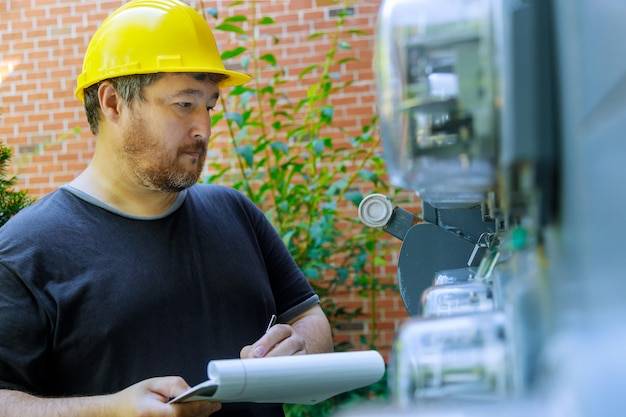 Close-up van elektrotechnisch ingenieur in gele helmtechnicus die op klembord vooraan zekeringkast schrijft