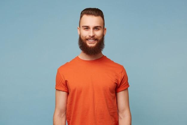 Close up van emotionele gelukkig grappige vriendje man met een zware baard gekleed in rood t-shirt geïsoleerd op blauw