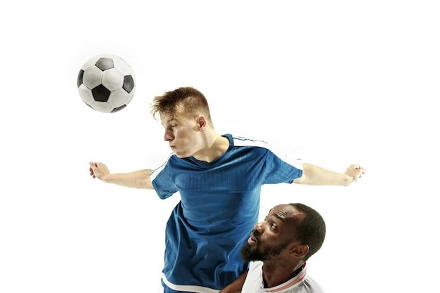 Close up van emotionele mannen voetballen die de bal raken met het hoofd op geïsoleerd op een witte muur. voetbal, sport, gezichtsuitdrukking, concept van menselijke emoties. kopieerruimte. vecht voor het doel.