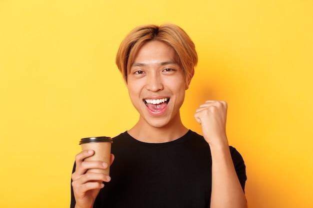 Close-up van energieke knappe aziatische man vuist pomp vreugdevol tijdens het drinken van koffie, glimlachend opgewonden over gele muur.
