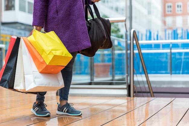 Close-up van enkele kleurrijke boodschappentassen vastgehouden door een vrouw in een winkelcentrum