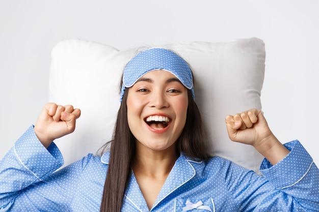 Close-up van enthousiast aziatisch meisje in blauwe pyjama en slaapmasker, handen uitstrekkend opgetogen na een goede nachtrust, oogmasker opstijgen in de ochtend, in bed op kussen liggen en gelukkig glimlachen