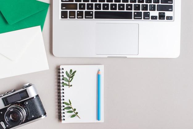 Close-up van enveloppen; vintage camera; spiraal notitieblok; gekleurd blauw potlood en laptop op grijze achtergrond