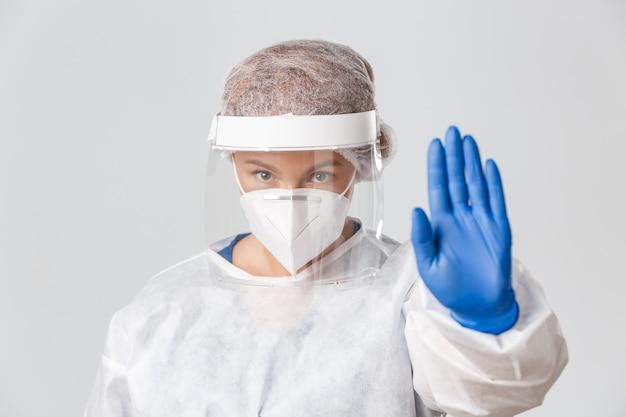 Close-up van ernstig ogende bezorgde vrouwelijke arts in persoonlijke beschermingsmiddelen, gelaatsscherm en gasmasker tonen stopgebaar, waarschuwing.