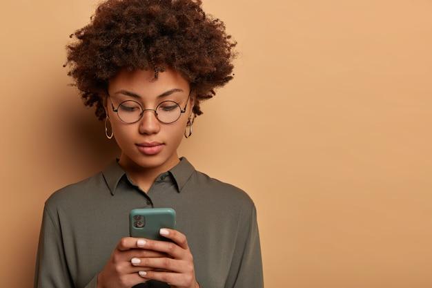 Close-up van ernstige afro-amerikaanse vrouw berichten op slimme telefoon typt