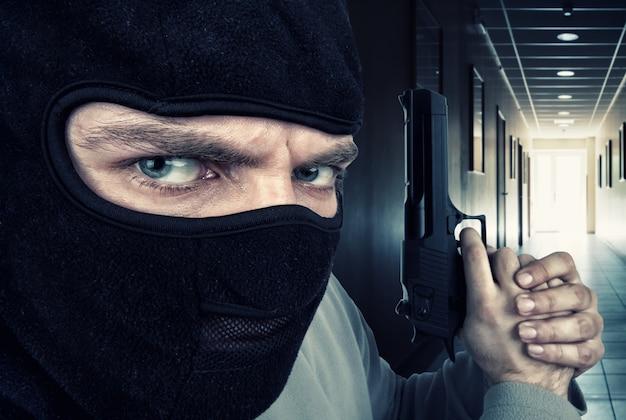 Close-up van ernstige gewapende crimineel met pistool