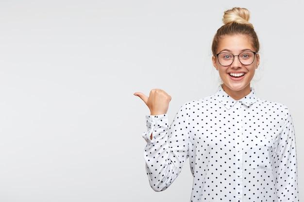 Close-up van ernstige mooie jonge vrouw met broodje draagt polka dot shirt en bril voelt zich gelukkig en wijst naar de zijkant