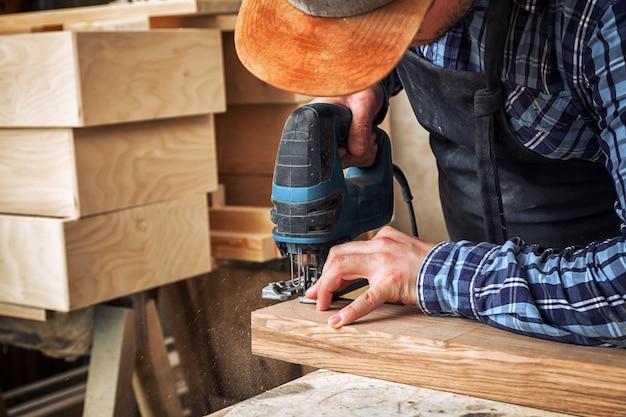 Close-up van ervaren timmerman zag en verwerkt de randen van een houten bar