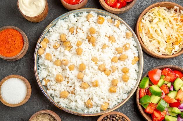 Close-up van erwten en rijst maaltijd zuurkool salade mayonaise kruiden en ketchup op donkere tafel