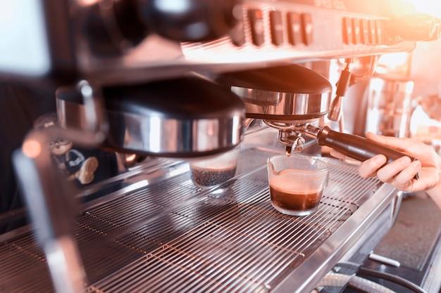 Close-up van espresso gieten uit koffiezetapparaat. professioneel koffie zetten, vintage stijl