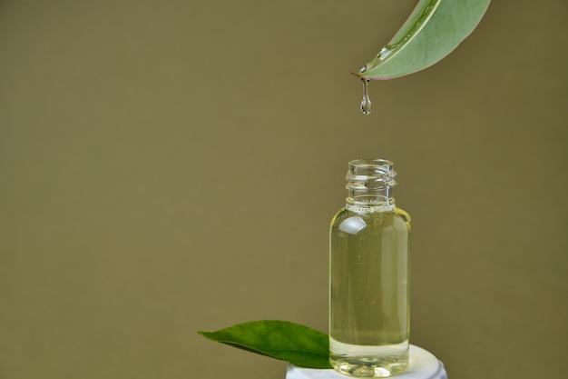 Close up van etherische olie druipend van vers natuurlijk blad in fles op olijfgroene achtergrond