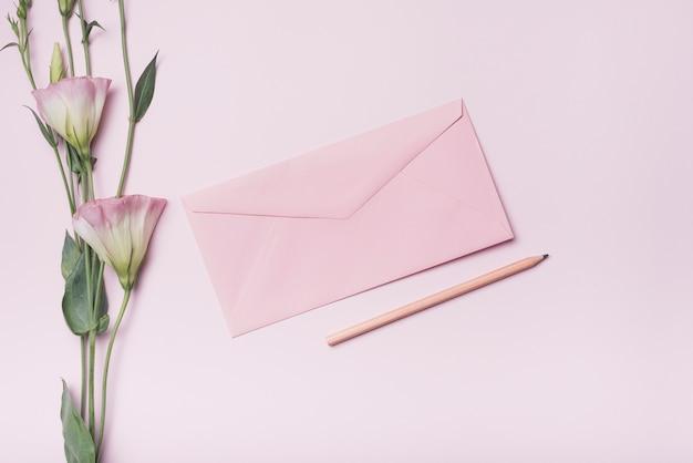 Close-up van eustomabloemen met envelop en potlood over roze achtergrond