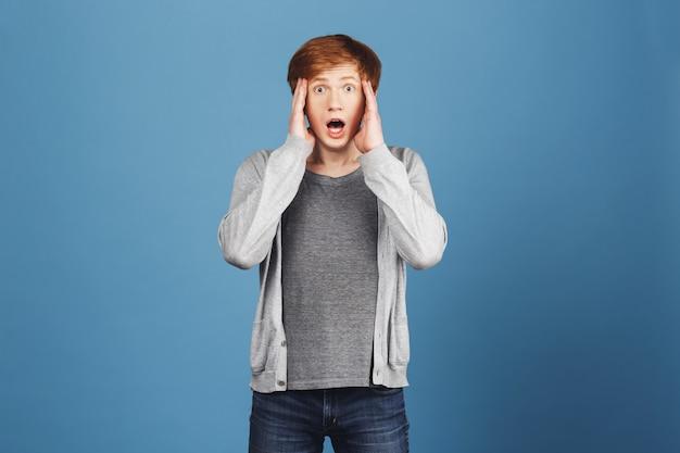 Close up van expressieve jonge knappe tiener man met rood haar in casual outfit hoofd met handen knijpen, geschokt zien beste vriend met zijn vriendin.