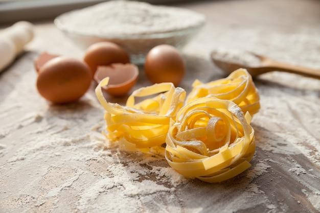 Close-up van fettuccine in kookproces met eieren en bloem op de achtergrond.