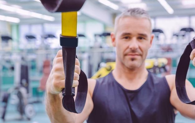 Close-up van fitnessriem in de hand van een man die een harde ophangingstraining doet in een fitnesscentrum. gezond en sportief levensstijlconcept.