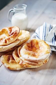 Close-up van flatbread pita met melk aan de wodden witte tafel. gefrituurde ohnny cake. oosterse keuken. azië flapjack. rustieke stijl.