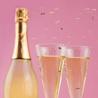 Close-up van fles champagne met glazen en confetti
