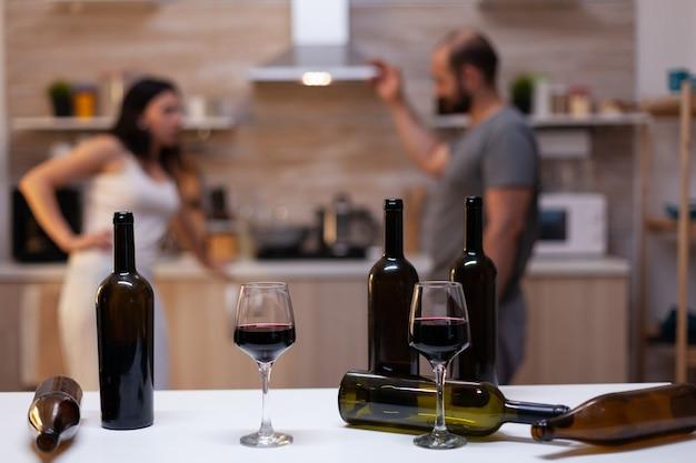 Close up van flessen en glazen gevuld met wijn, sterke drank, drank en alcoholische drank voor alcoholverslaafden op de achtergrond chatten. dronken dronken mensen met ongezonde verslaving