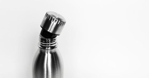 Close-up van flessenhals met open dop op witte achtergrond met kopie ruimte. herbruikbare stalen thermo waterflessen. geen plastic afval.