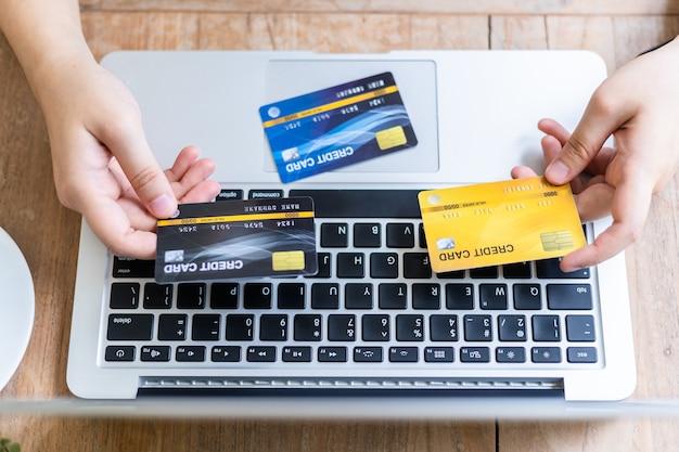 Close-up van freelance mensen zaken vrouw hand met creditcards casual werken met laptop