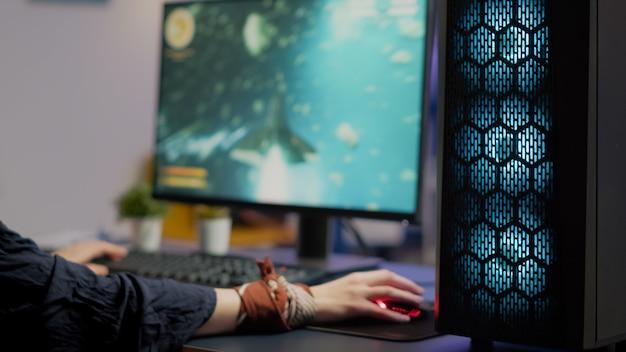 Close-up van gamer met behulp van professionele rgb-muis en toetsenbord die space shooter-toernooi spelen in gaming-thuisstudio. pro-speler die online videogame streamt tijdens virtueel kampioenschap op krachtige computer