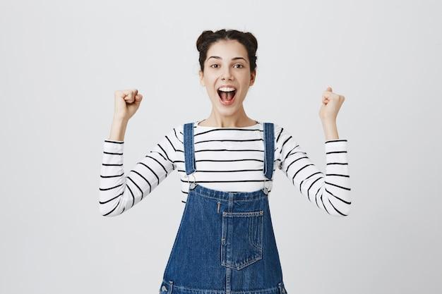 Close-up van geamuseerd en vrolijk meisje dat triomfeert, zich verheugt over de overwinning, viert