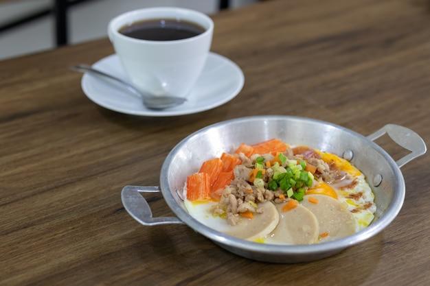 Close-up van gebakken eieren, gehakt varkensvlees, krabstick en varkensworst als ontbijt en geserveerd met koffie