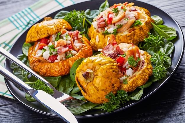 Close-up van gebakken pattypan squash gevuld met rijst, gebakken kippenvlees, krokant gebakken spek, rode paprika en geserveerd met spinazieblaadjes en peterselie op een zwarte plaat met vork en mes
