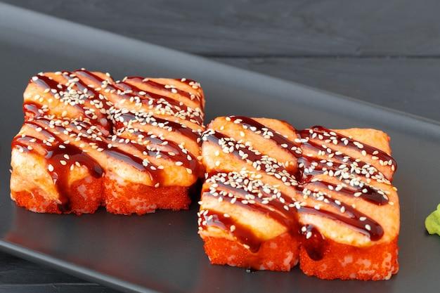Close-up van gebakken sushi roll geserveerd op zwarte plaat op houten tafel