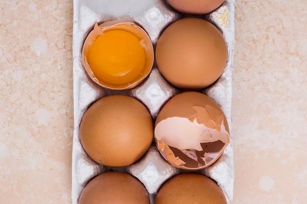 Close-up van gebroken eieren in witte doos op textuur achtergrond