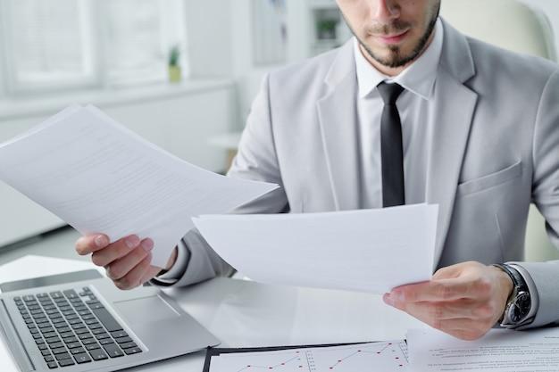 Close-up van geconcentreerde jonge bebaarde manager zit aan bureau in kantoor en het analyseren van documentinhoud