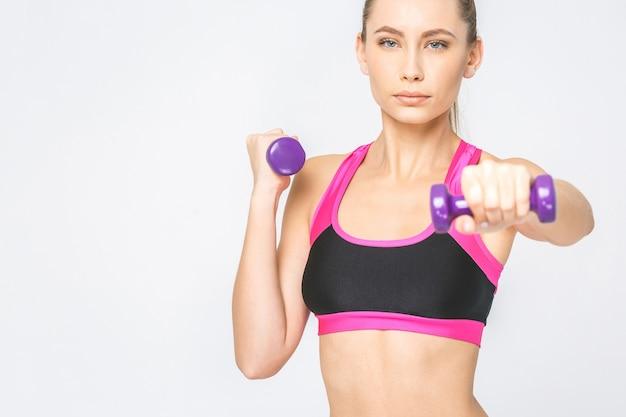 Close-up van geconcentreerde, serieuze jonge fitness vrouw die halters opheft glimlachend en energiek