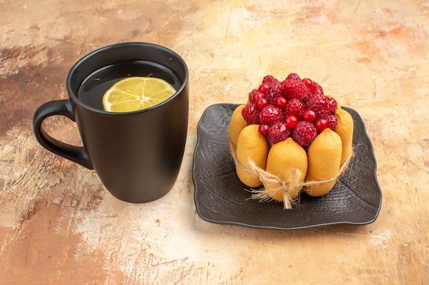 Close-up van gedekte tafel met een cake van de gift en thee in een zwarte kop met citroen op gemengde kleurentafel