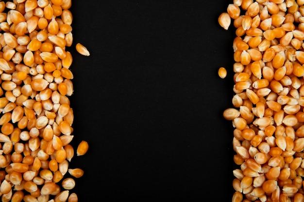 Close-up van gedroogde maïs zaden aan de linker- en rechterkant en een zwarte achtergrond met kopie ruimte