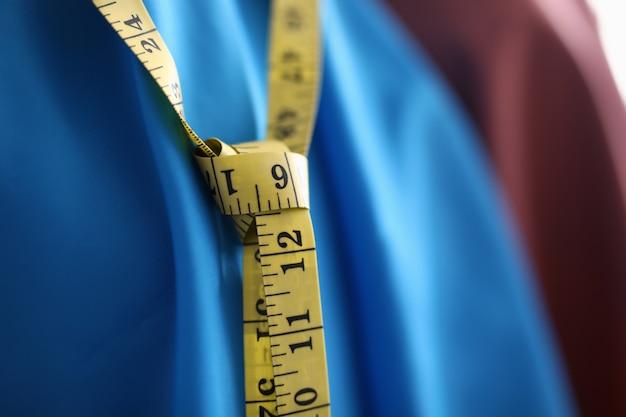Close-up van geel meetlint op stijlvol blauw kostuum. naaipakken op bestelling. kwaliteits textiel en assortiment kleuren. modefabriek en atelierconcept