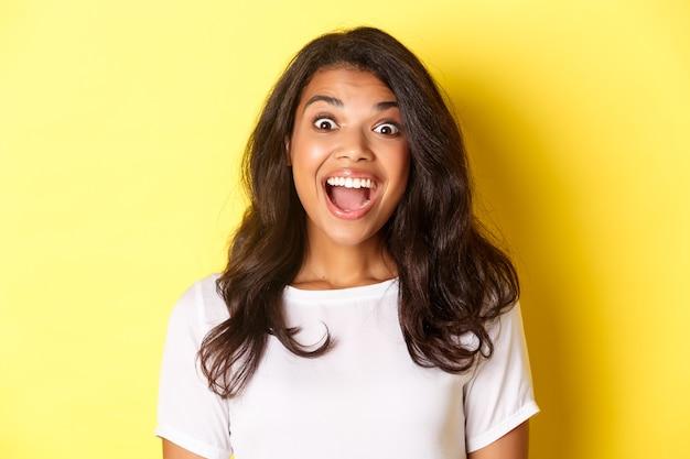 Close-up van gefascineerd afro-amerikaans meisje met open mond en verbaasd kijkend naar iets cools dat staat ...