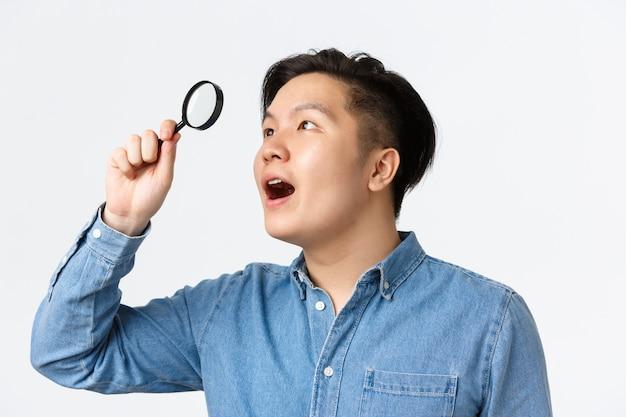 Close-up van gefascineerde aziatische man, onderzoeker in blauw shirt, kijkend door vergrootglas in linkerbovenhoek met verbaasde uitdrukking, vond iets interessants, witte muur