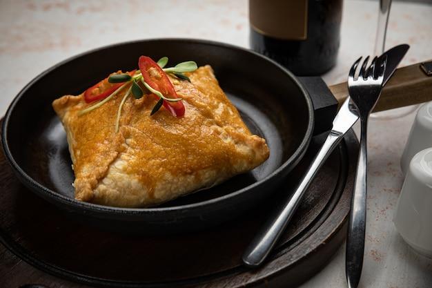 Close-up van gefrituurde omzet met een vulling van rundergehakt en ui in een zwarte keramische pan op een witte tafel