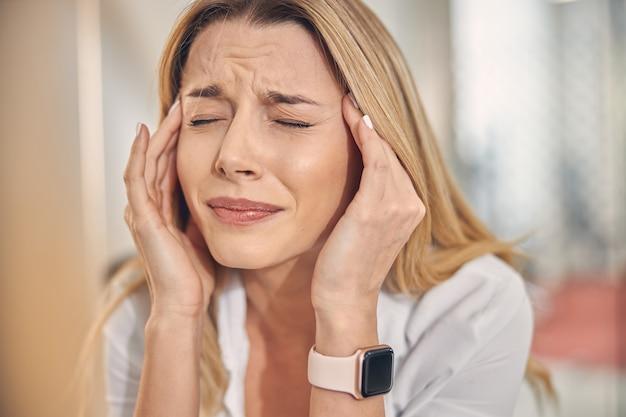 Close up van gefrustreerde dame met slim horloge om haar pols die lijdt aan migraine