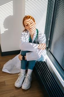 Close-up van gefrustreerde trieste jonge vrouwelijke arts in witte jas zittend op de vloer knuffelen benen met handen in de buurt van raam.