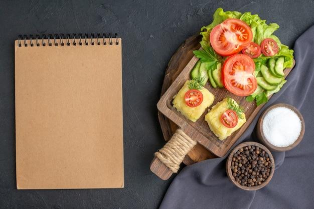 Close-up van gehakte verse groenten kaas op snijplank en kruiden op donkere kleur handdoek notebook op zwarte ondergrond