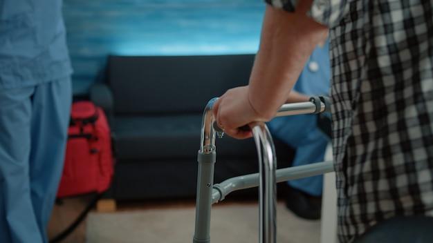Close up van gehandicapte patiënt met hand op loopframe