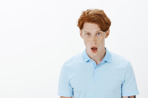 Close-up van geïmponeerde roodharige man laat zijn kaak vallen en hijgt van verbazing
